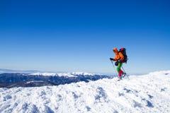 Invierno que camina en las montañas en las raquetas con una mochila y una tienda Fotos de archivo libres de regalías