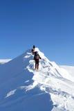 Invierno que camina en las montañas en las raquetas con una mochila y una tienda Foto de archivo