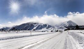 Invierno y nieve en el camino que lleva a las montañas imagen de archivo