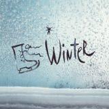 Invierno y patines de la inscripción en la ventana congelada fotos de archivo