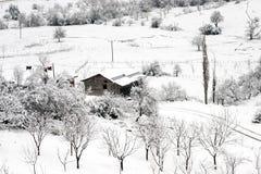 Invierno y una choza del pueblo Fotos de archivo libres de regalías