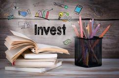 Invierta, concepto del negocio Pila de libros y de lápices en la tabla de madera imagen de archivo