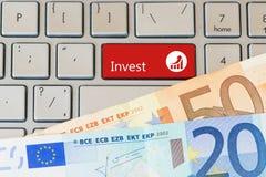 Invierta el botón rojo en el teclado del ordenador portátil con los billetes de banco euro Opinión del primer imagen de archivo libre de regalías