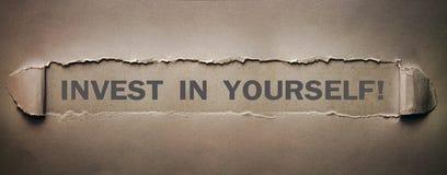 Invierta en sí mismo la palabra en el papel rasgado foto de archivo libre de regalías