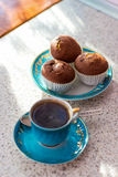 Invigorating cup of coffee with cupcakes is on the table for breakfast Stock Photography