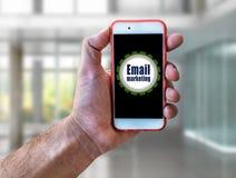 Invii con la posta elettronica l'introduzione sul mercato, cellulare della tenuta della mano di concetto di vendita Fotografia Stock