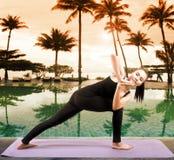 Invio asiatico di yoga di sanità della donna accanto alla piscina immagine stock