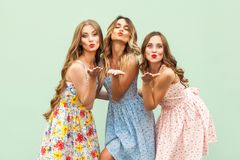 Invio del bacio dell'aria Tre migliori amici che posano nello studio, vestito d'uso da stile di estate contro fondo verde immagini stock