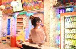 Invio della donna davanti ai distributori automatici giapponesi variopinti fotografia stock libera da diritti