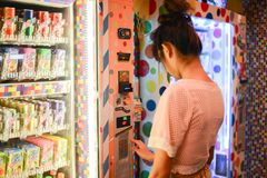 Invio della donna davanti ai distributori automatici giapponesi variopinti fotografie stock libere da diritti