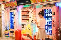 Invio della donna davanti ai distributori automatici giapponesi variopinti fotografie stock