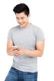 Invio di messaggi di testo del giovane sul telefono cellulare fotografie stock