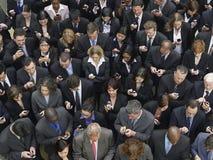 Invio di messaggi di testo del gruppo di affari con i telefoni cellulari Fotografie Stock Libere da Diritti