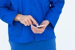 Invio di messaggi di testo del meccanico sul telefono cellulare fotografia stock
