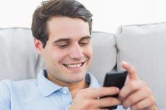 Invio di messaggi di testo dell'uomo con il suo telefono immagini stock libere da diritti