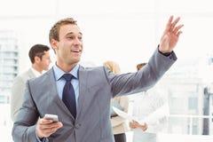 Invio di messaggi di testo dell'uomo d'affari con i colleghi nella riunione dietro fotografia stock libera da diritti