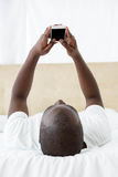 Invio di messaggi di testo dell'uomo sul telefono cellulare in camera da letto fotografie stock libere da diritti