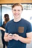Invio di messaggi di testo dell'uomo sullo smartphone immagini stock