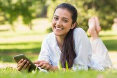 Invio di messaggi di testo della donna mentre rilassandosi nel parco immagine stock