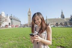 Invio di messaggi di testo della giovane donna tramite lo Smart Phone contro Big Ben a Londra, Inghilterra, Regno Unito Immagini Stock