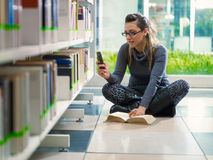 Invio di messaggi di testo della ragazza con il telefono in libreria Immagini Stock