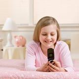 Invio di messaggi di testo della ragazza sul telefono delle cellule nella sua camera da letto fotografie stock