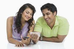 Invio di messaggi di testo delle coppie sui telefoni cellulari Fotografie Stock Libere da Diritti
