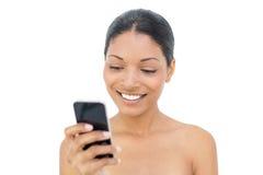 Invio di messaggi di testo di modello moro sorridente Immagini Stock