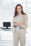 Invio di messaggi di testo elegante sorridente della donna di affari in ufficio immagine stock