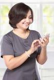 Invio di messaggi di testo felice della donna di affari fotografia stock libera da diritti