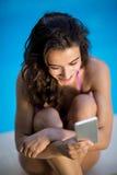 Invio di messaggi di testo felice della donna su un telefono cellulare fotografia stock