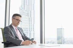 Invio di messaggi di testo maturo dell'uomo d'affari tramite il telefono cellulare vicino alla finestra dell'ufficio fotografie stock libere da diritti