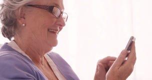 Invio di messaggi di testo senior della donna sul telefono cellulare stock footage