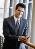Invio di messaggi di testo sicuro dell'uomo d'affari sul telefono delle cellule fotografie stock
