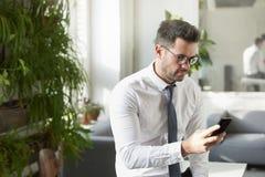 Invio di messaggi di testo dell'uomo d'affari mentre sedendosi nel offce fotografie stock libere da diritti