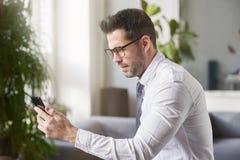 Invio di messaggi di testo dell'uomo d'affari mentre sedendosi nel offce immagini stock