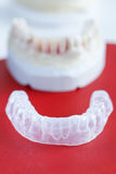 Invisalign, invisible plastic teeth aligner. With dental plaster mold in the background Stock Image