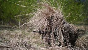 Invisible camouflaged army military man in camouflage among the grass sniper with an automatic rifle in hands. Invisible camouflaged army military man in stock video