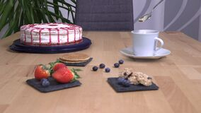 Invisible ghost stirs coffee, cake with cookies stand on the table