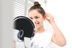 Invisible hearing aid. Cheerful girl assumes hearing aid viewing in the mirror Stock Photography