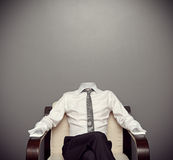 Invisible man sitting on armchair. Invisible man in formal wear sitting on armchair against grey background Stock Image