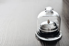 Invisible service. Service bell in glass mini dome on wooden background Stock Photo