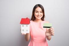 Invista no conceito dos bens imobiliários Mulher que guarda a casa pequena do brinquedo e Foto de Stock Royalty Free