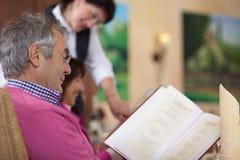 Invité dans le restaurant lisant le menu Image stock