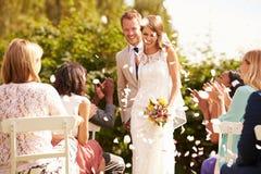 Invités jetant des confettis au-dessus des jeunes mariés At Wedding Photos libres de droits