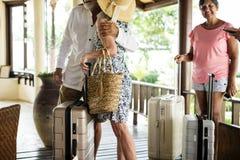 Invités supérieurs arrivant à un compteur de station de vacances de réservation image stock
