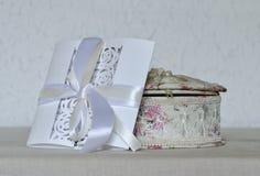 Invitación blanca en el fondo blanco, caja, espacio de la boda para el texto Fotos de archivo