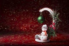 Invitación del Año Nuevo Imagen de la Navidad con un muñeco de nieve del juguete en un fondo rojo Fotos de archivo