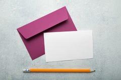 Invitación a una boda o a un cumpleaños Una hoja de papel en blanco con el espacio para el texto, un sobre rosado y un lápiz en u foto de archivo libre de regalías