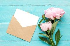 Invitaci?n de la boda tarjeta y sobre en blanco de felicitación con el ramo de las flores de la peonía en fondo de madera azul En fotos de archivo